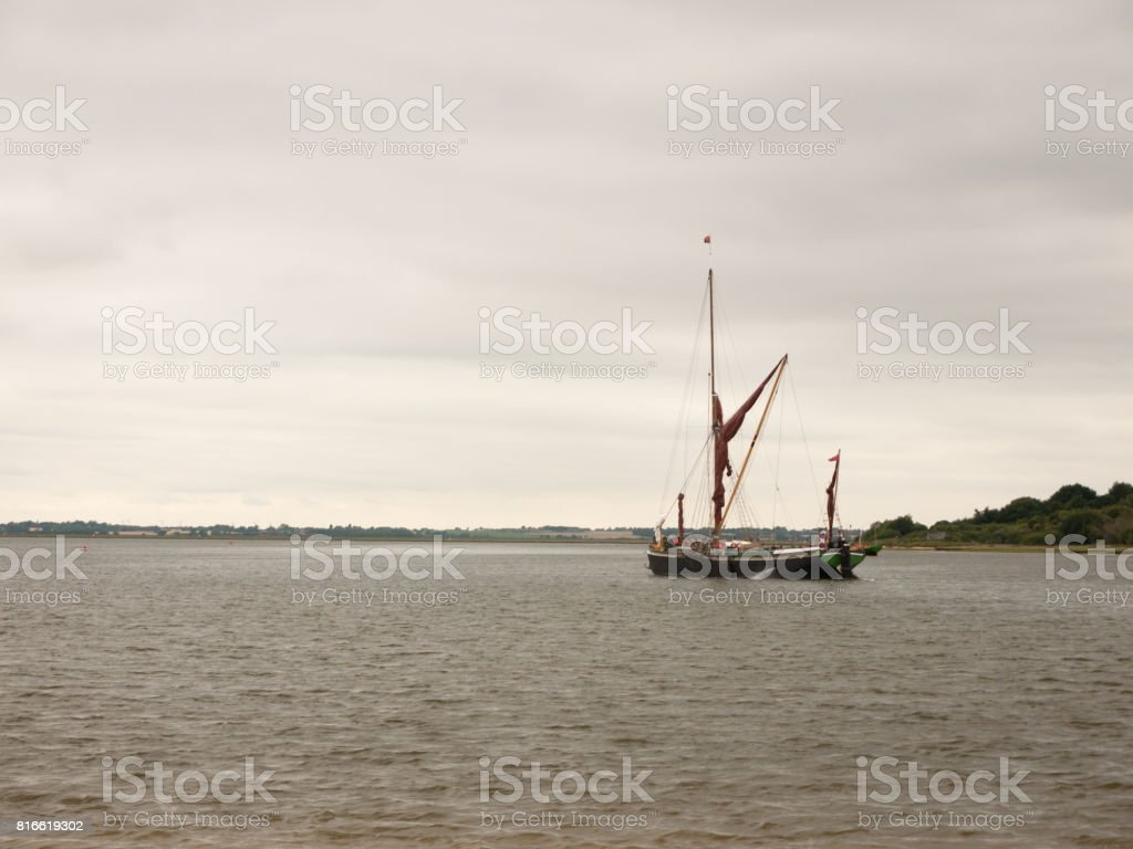 A London Barge Sailing down the River Colne into open Sea stock photo