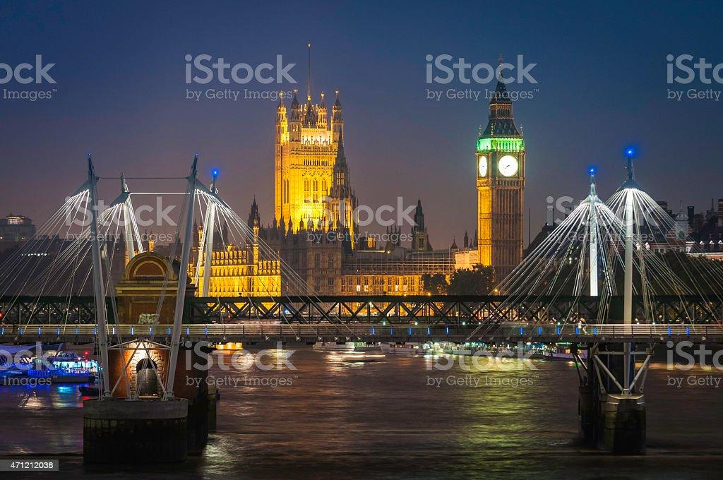 London Big Ben Parliament illuminated over River Thames Jubilee Bridge stock photo