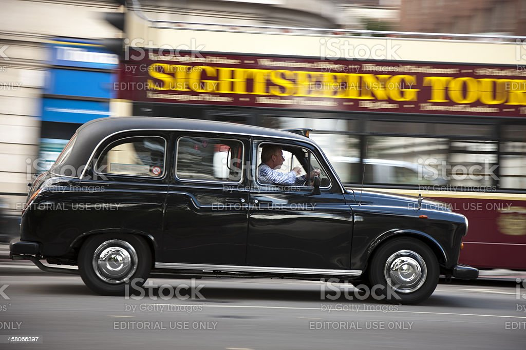 London Black Taxi Cab Driving in Front of Sightseeing Bus stock photo