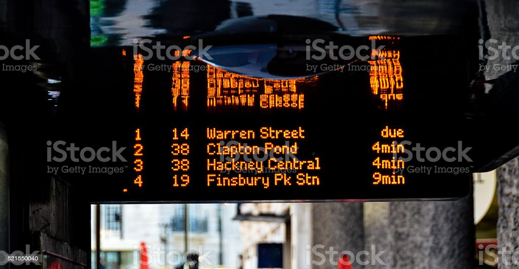 London bus stop with arrival sign stock photo