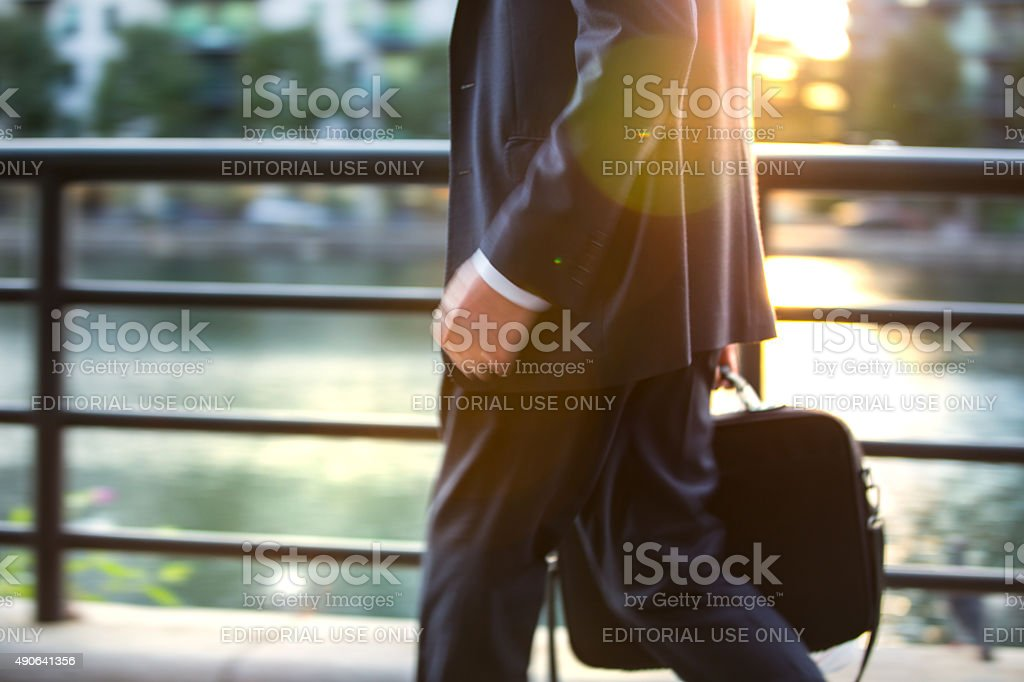 London, businessman walking on street against of sunset stock photo