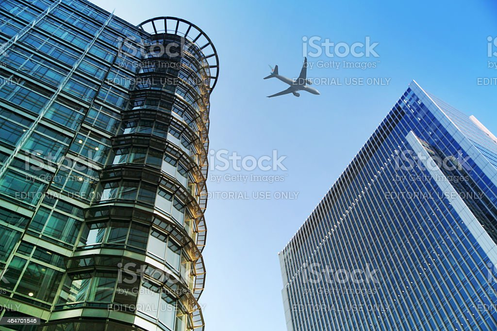 London, office buildings and airplane in the blue sky stock photo