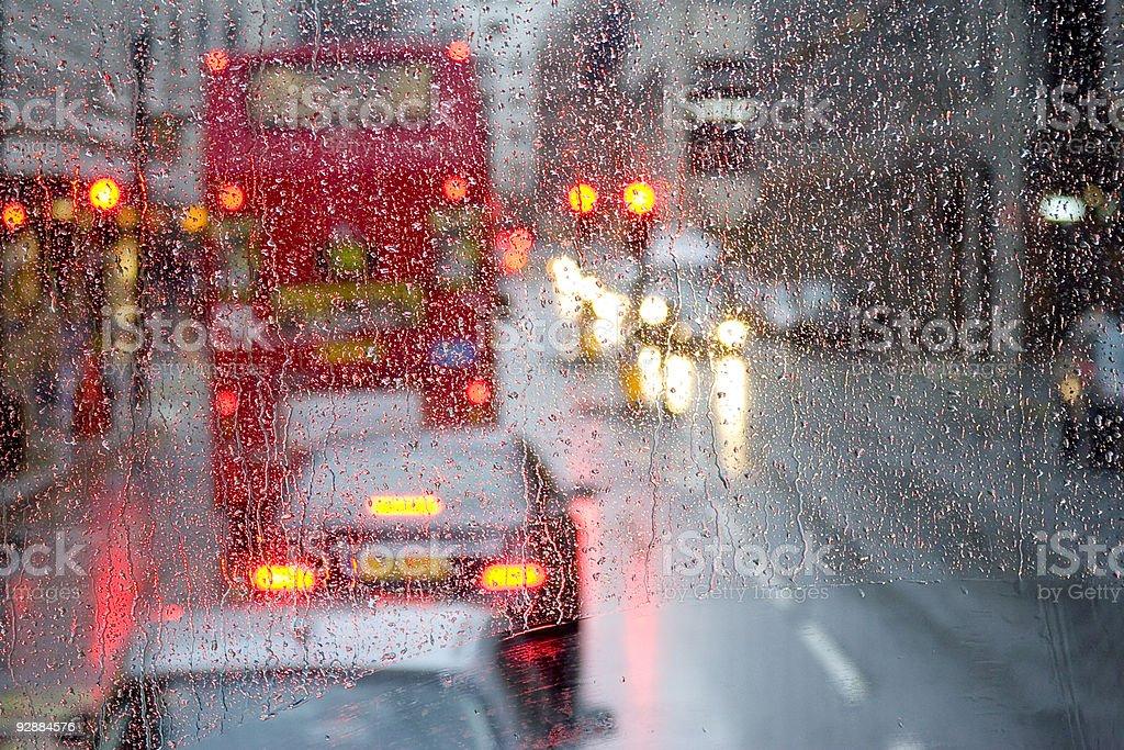 London rain view to red bus through rain-specked window stock photo