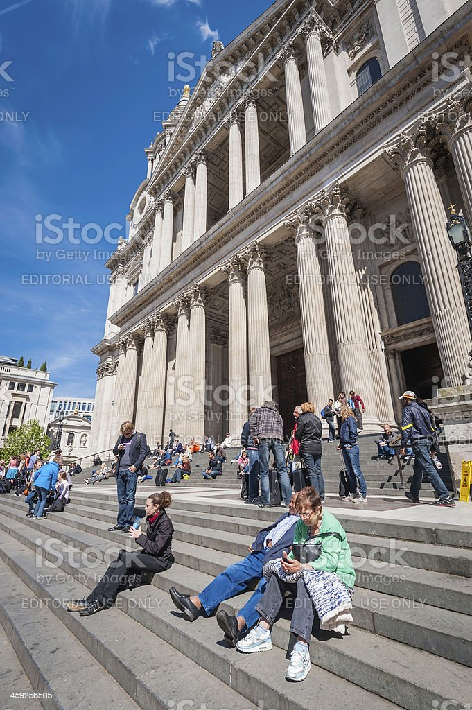 London tourists relaxing on steps of St Pauls Cathedral royalty-free stock photo