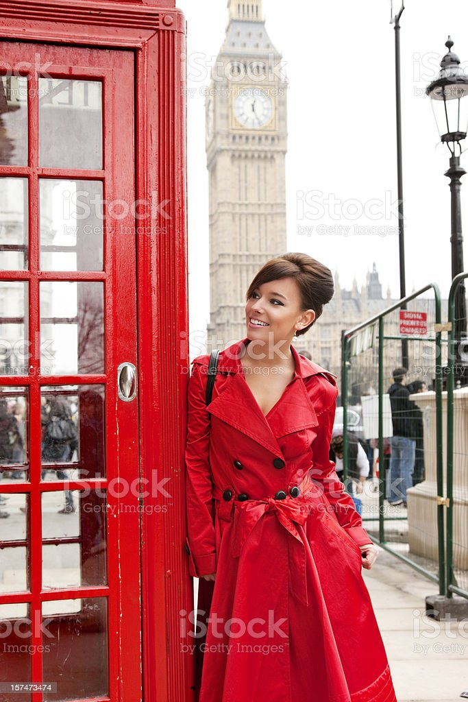London Woman in Red Leaning on Phone Booth stock photo