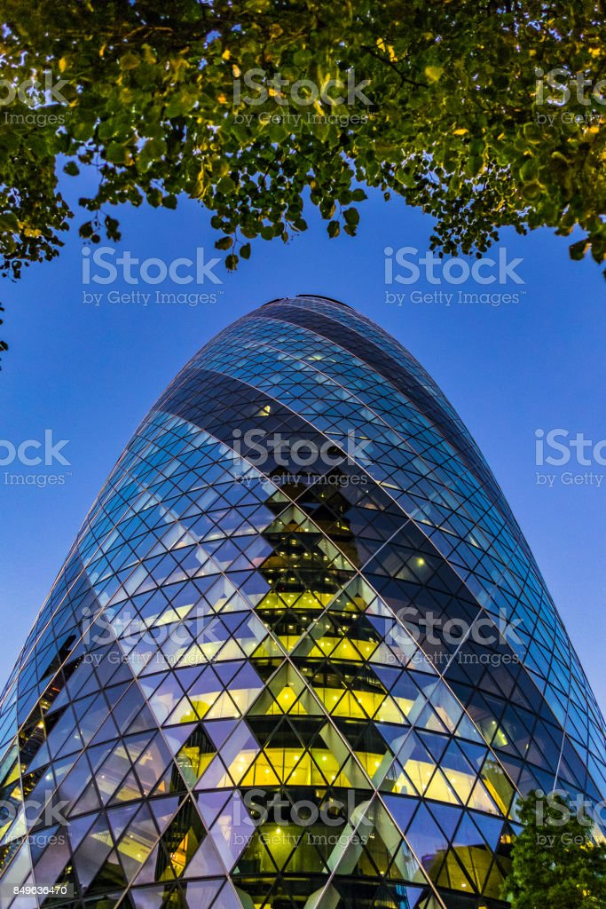 London's iconic Gherkin tower framed by green tree overhang stock photo
