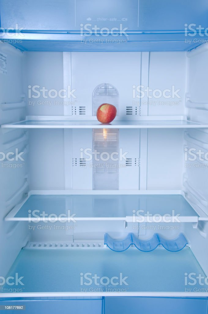 Lone Apple Sitting in Empty Refrigerator royalty-free stock photo