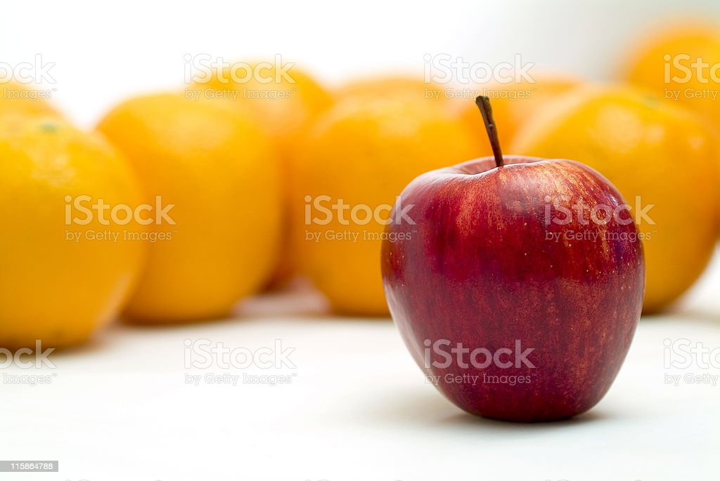 Lone apple standing in front of several blurred oranges stock photo