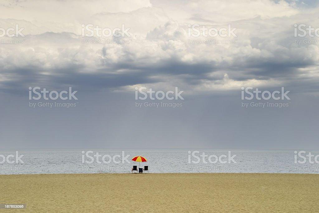 Lone beach umbrella facing advancing storm stock photo