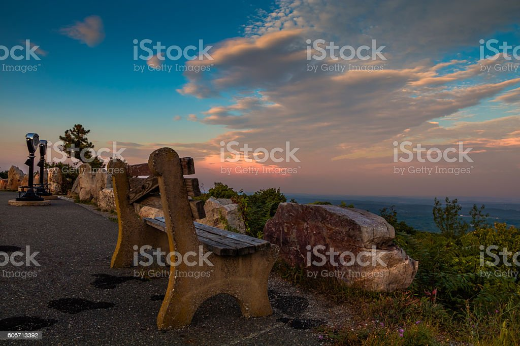 Lone bench and viewing binoculars at sunset stock photo