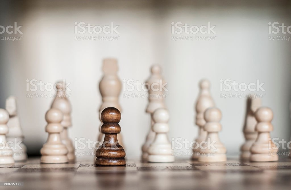 Lone Black Pawn Amongst Many White Pieces stock photo