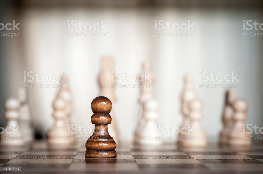 Lone Black Pawn Facing A White Army stock photo
