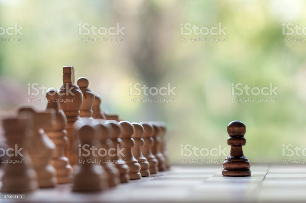 Lone Black Pawn Facing An Army stock photo