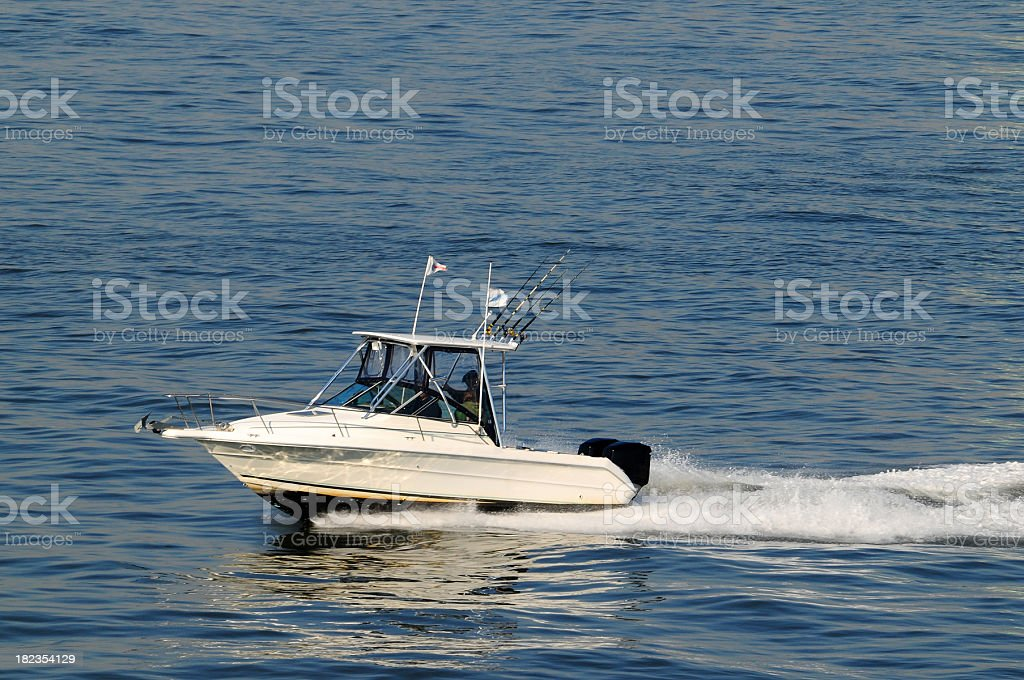 Lone boat in the ocean during a fishing trip stock photo
