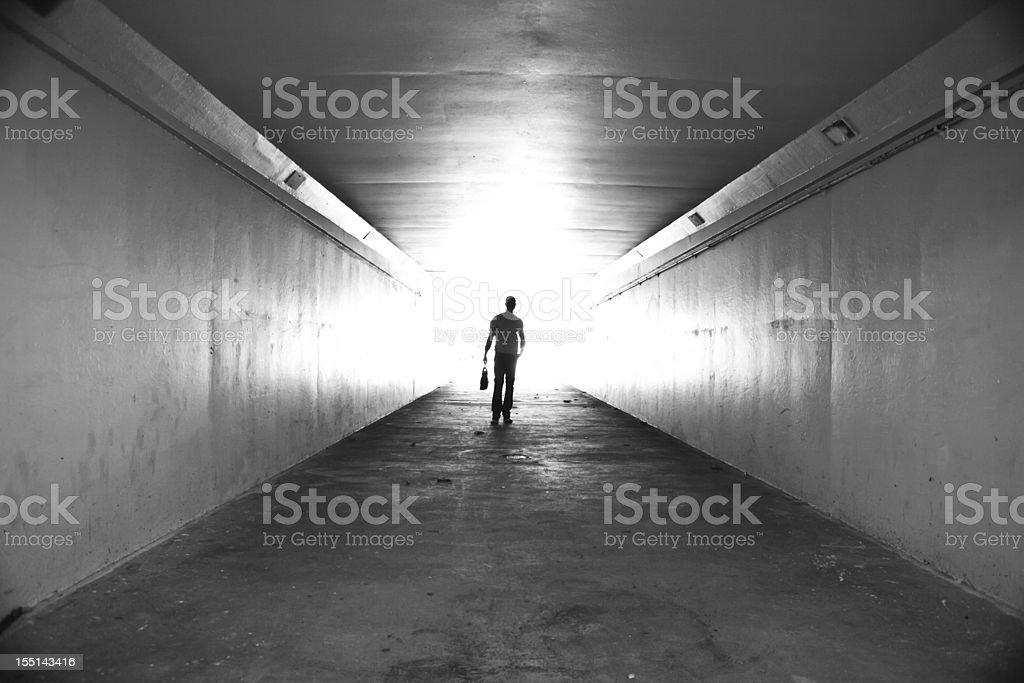 Lone businessman walking through tunnel with briefcase royalty-free stock photo