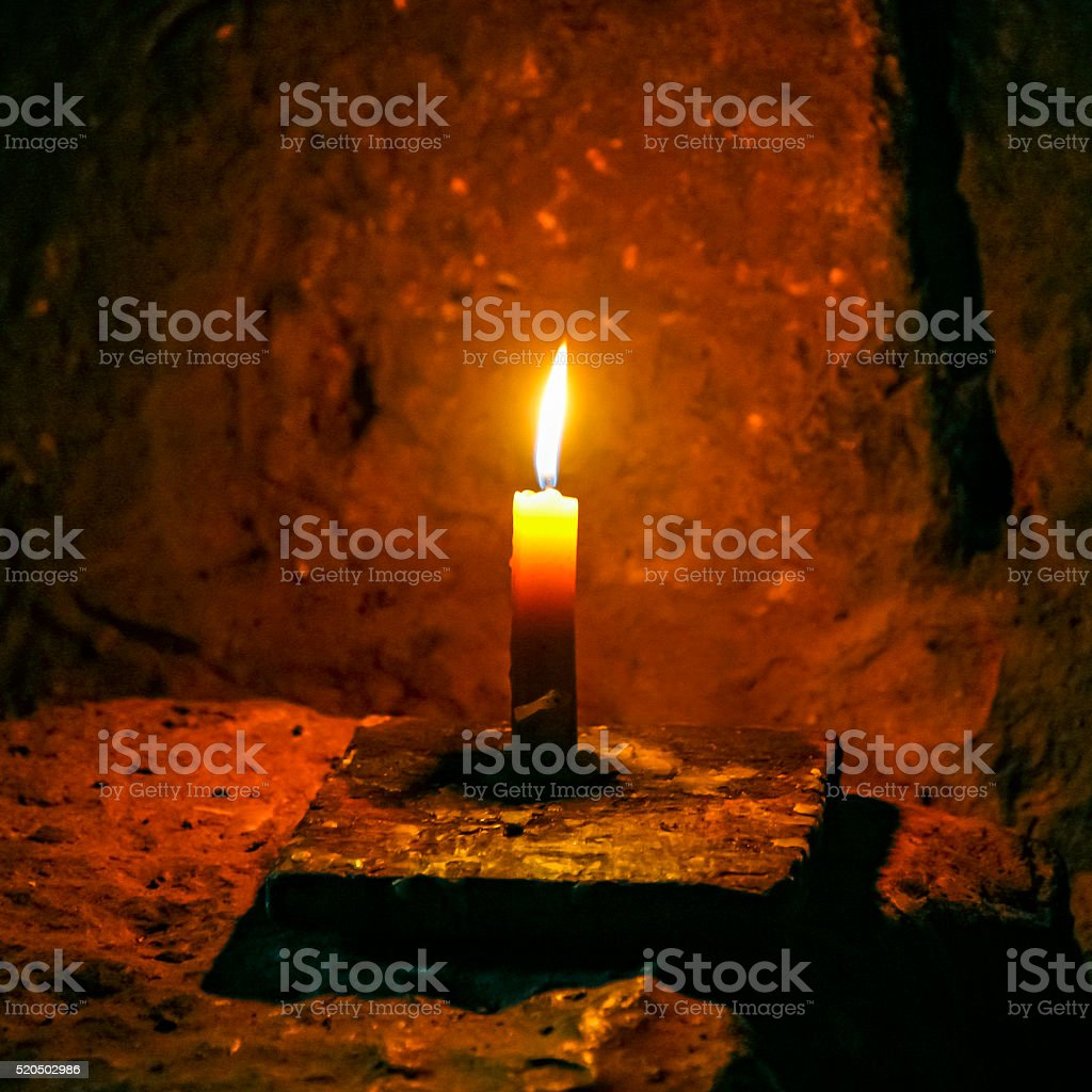 Lone candle burns brightly in darkness of Angkor Wat stock photo