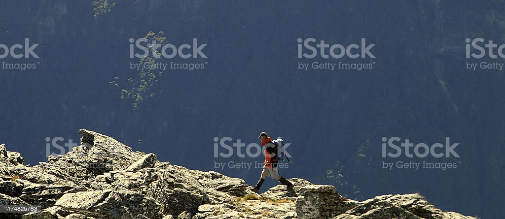 Lone climber on rock outcrop, Nelson, New Zealand stock photo