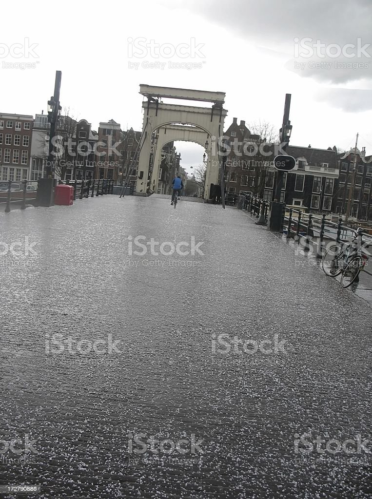 Lone cyclist on Amsterdam bridge during hailstorm royalty-free stock photo