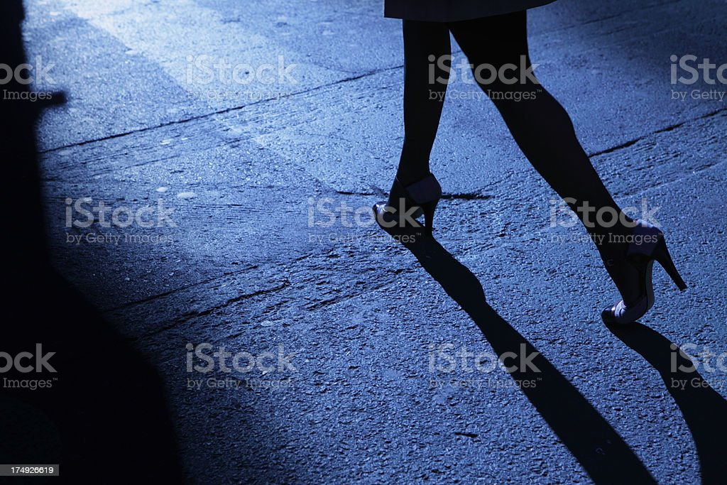 Lone female stiletto heels walking in blue night shadows stock photo