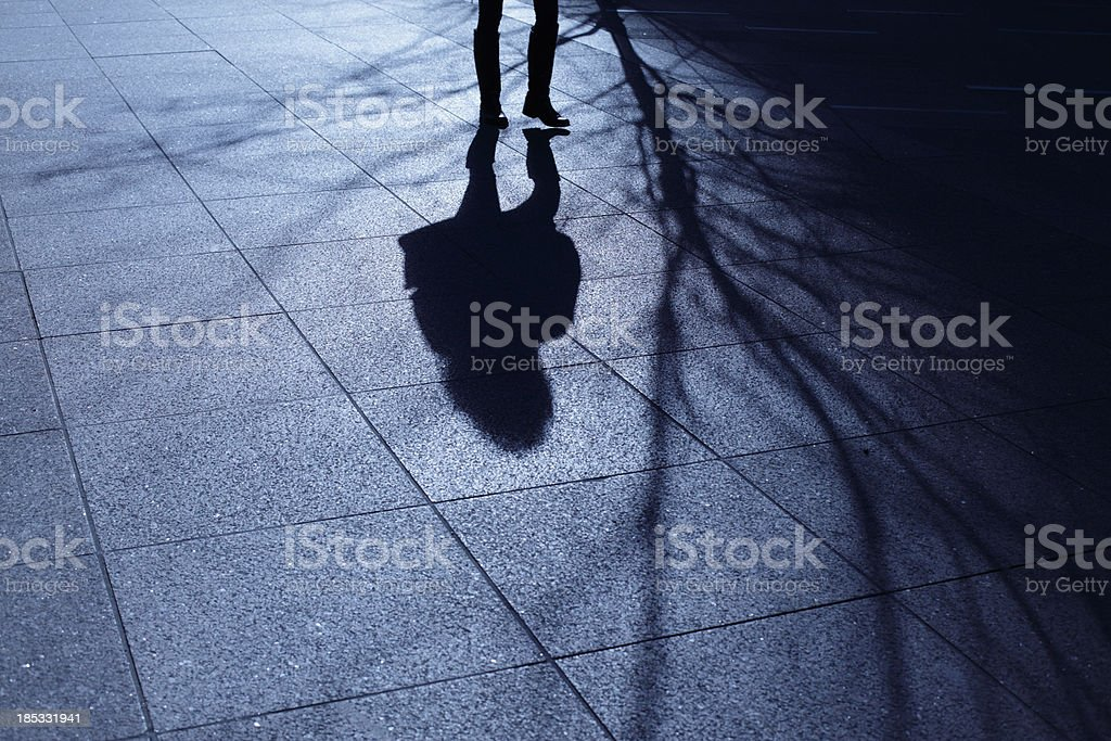 Lone female walking in blue night shadows royalty-free stock photo