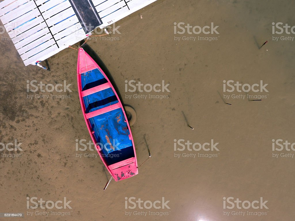 Lone fishing boat floating on a landing stage stock photo