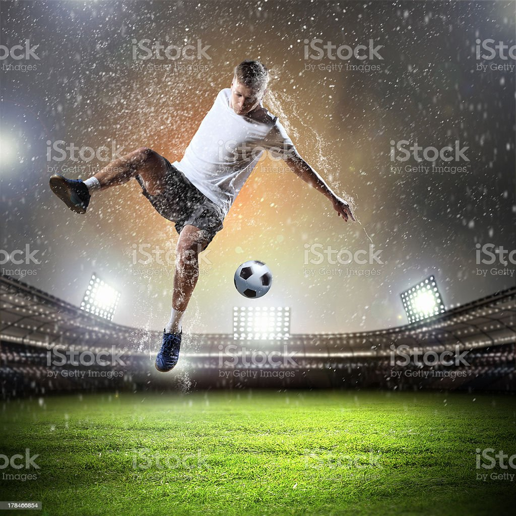Lone footballer in midair with ball at stadium royalty-free stock photo
