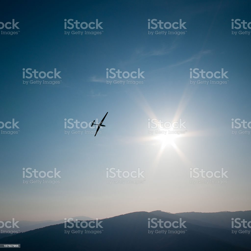 lone glider flies to the sun, mountain panorama and sky stock photo