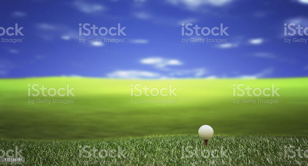 Lone golf ball sitting on green field under the blue sky royalty-free stock photo