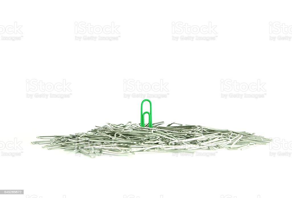 Lone green paperclip standing out in the crowd foto de stock libre de derechos