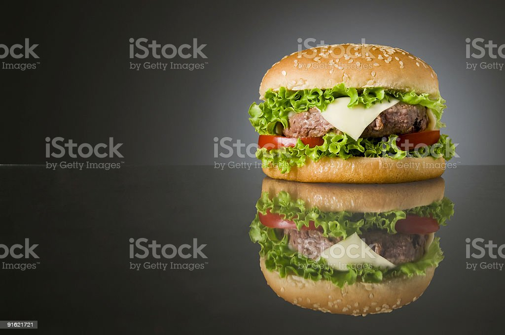 Lone hamburger and its reflection over a gray surface stock photo