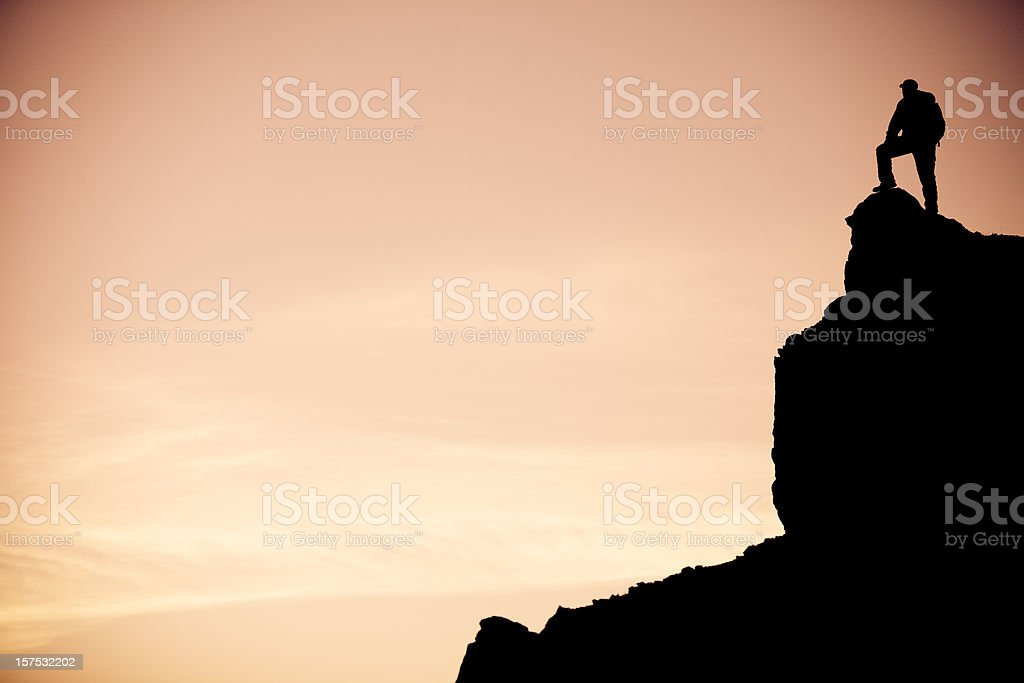 Lone hiker enjoys the sunrise view from a cliff royalty-free stock photo