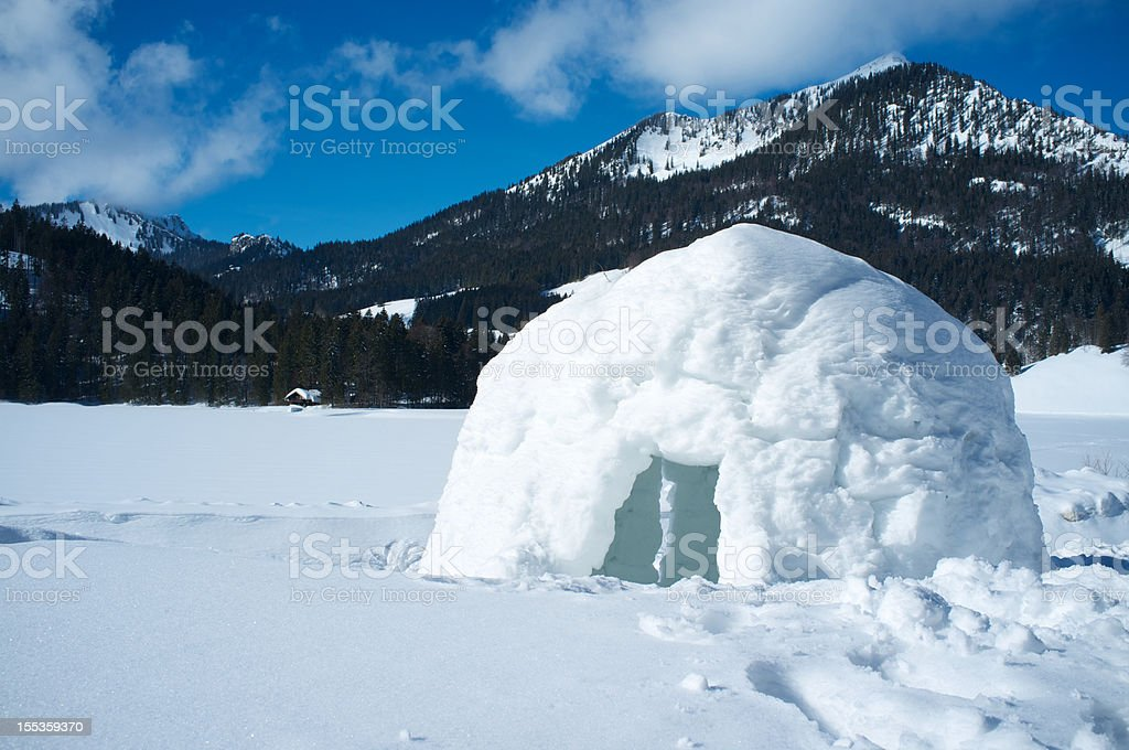A lone igloo in a mountainous scene stock photo