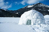 A lone igloo in a mountainous scene