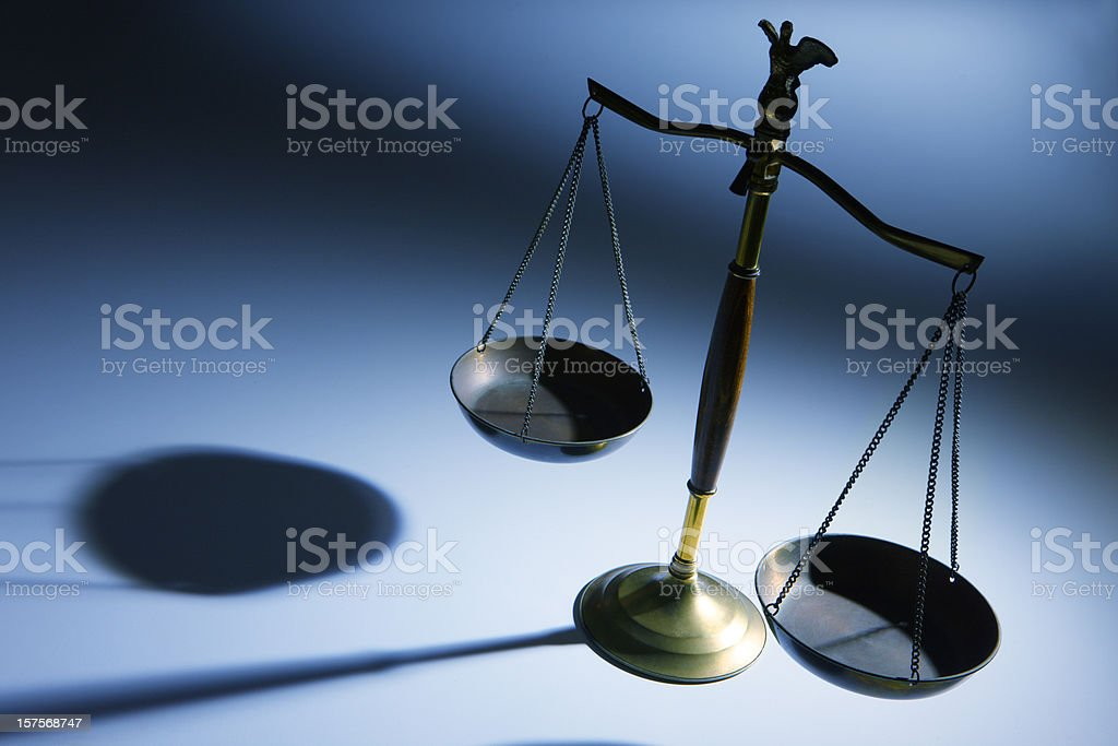 Lone justice scale on simple blue background royalty-free stock photo