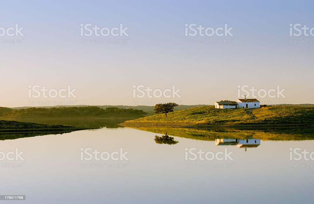 Lone lake house standing on a hill by a still lake stock photo