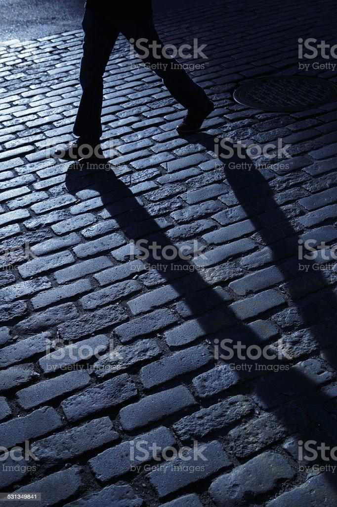 Lone man walking in blue night shadows stock photo