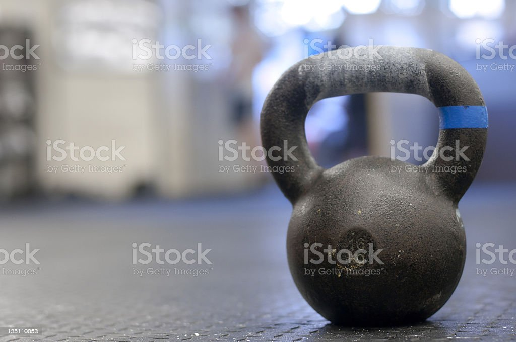 Lone metal 16 kg kettlebell over a blurred gym background stock photo
