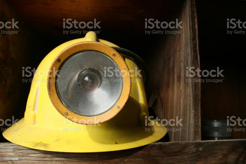 Lone mining helmet sitting on a wood shelf royalty-free stock photo