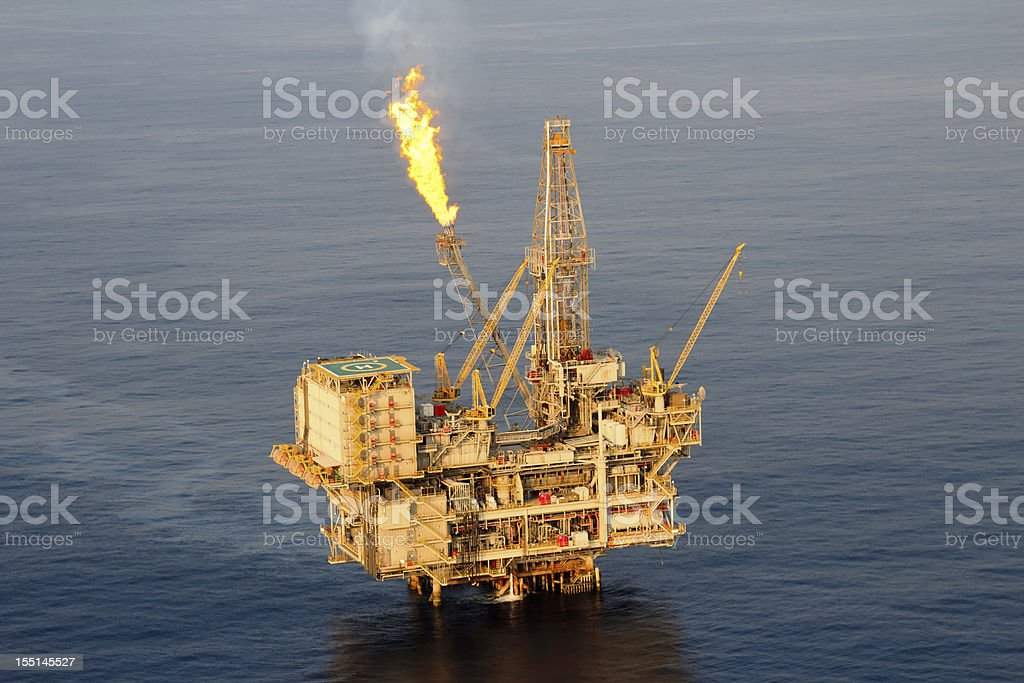 Lone oil rig in middle of sea  stock photo