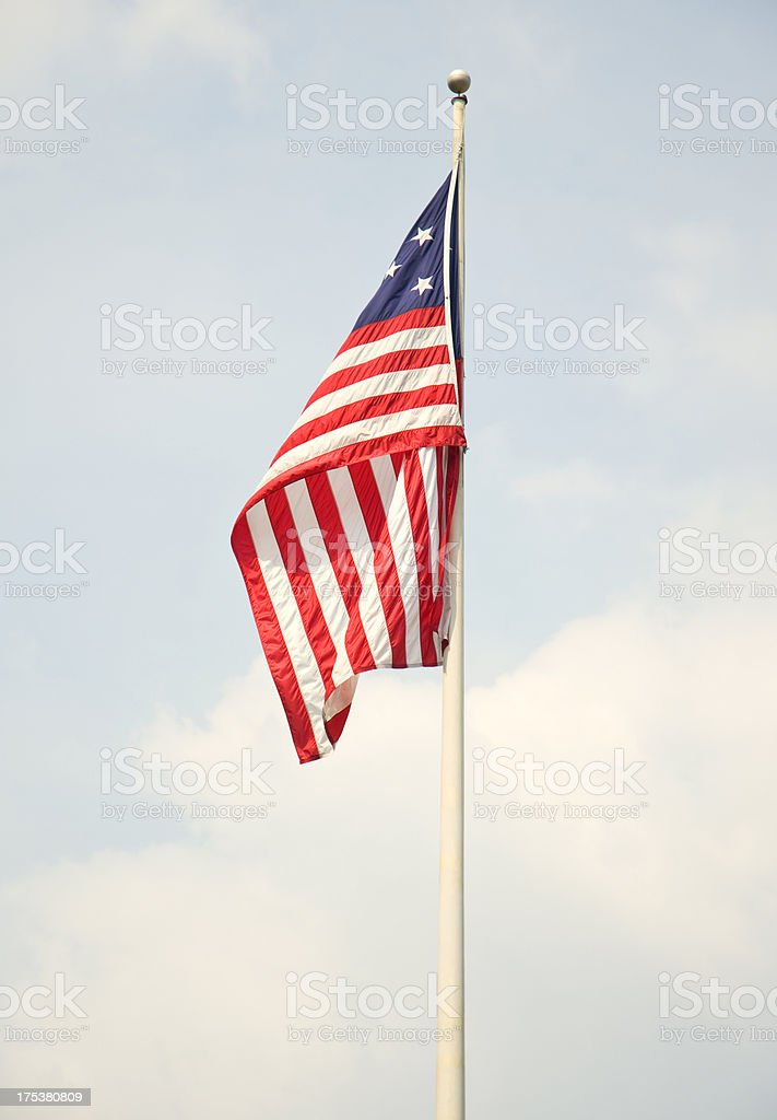 Lone Patriotic American Flag Against A Blue Sky On Flagpole royalty-free stock photo