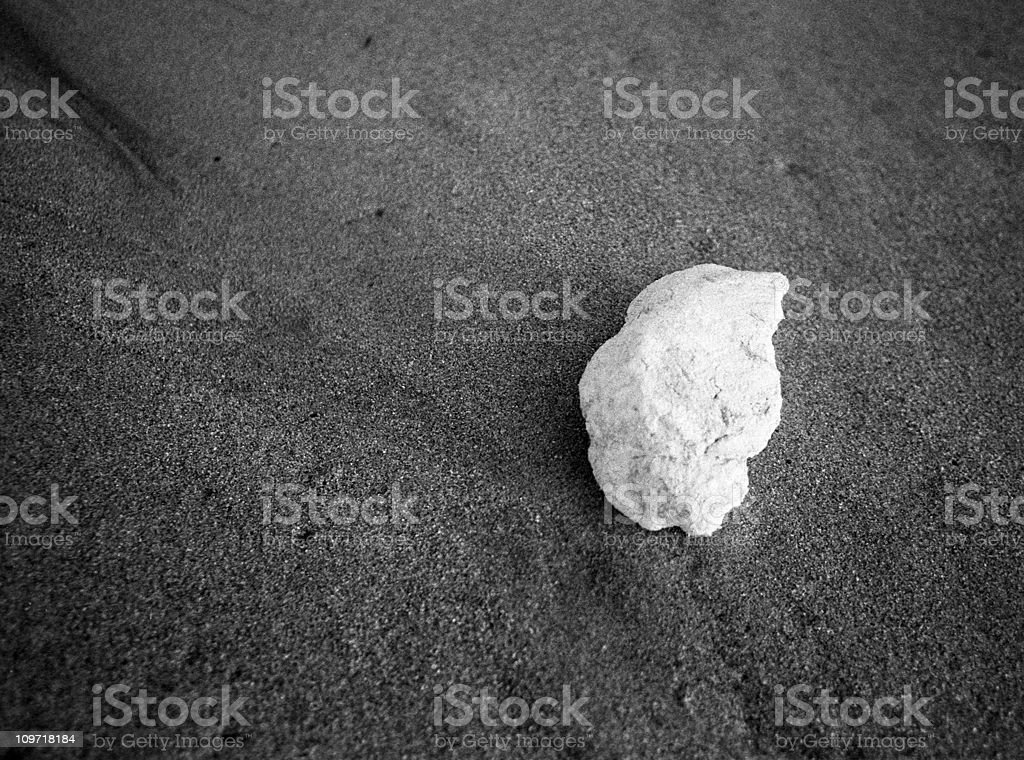 Lone Pebble on Sand Beach, Black and White stock photo
