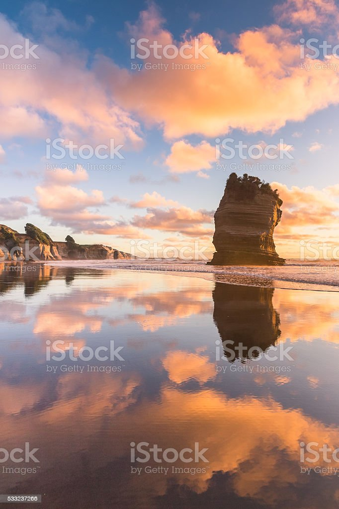 Lone rock and sunset sky reflection stock photo
