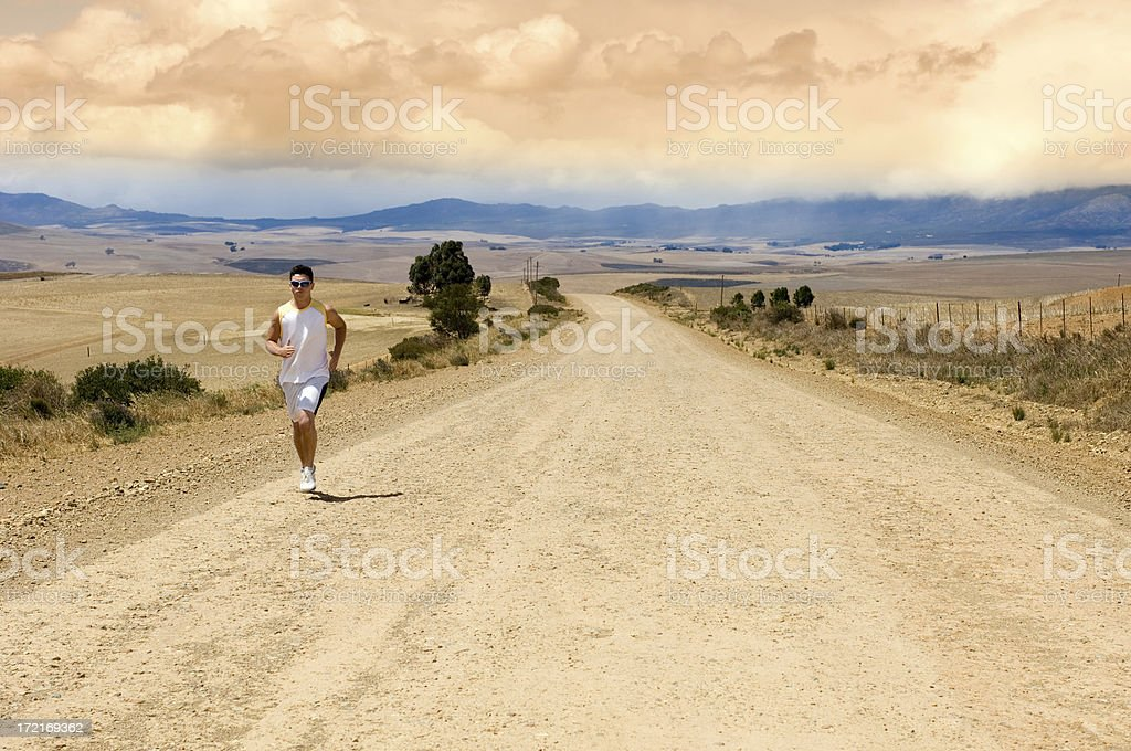 Lone runner on a long road stock photo