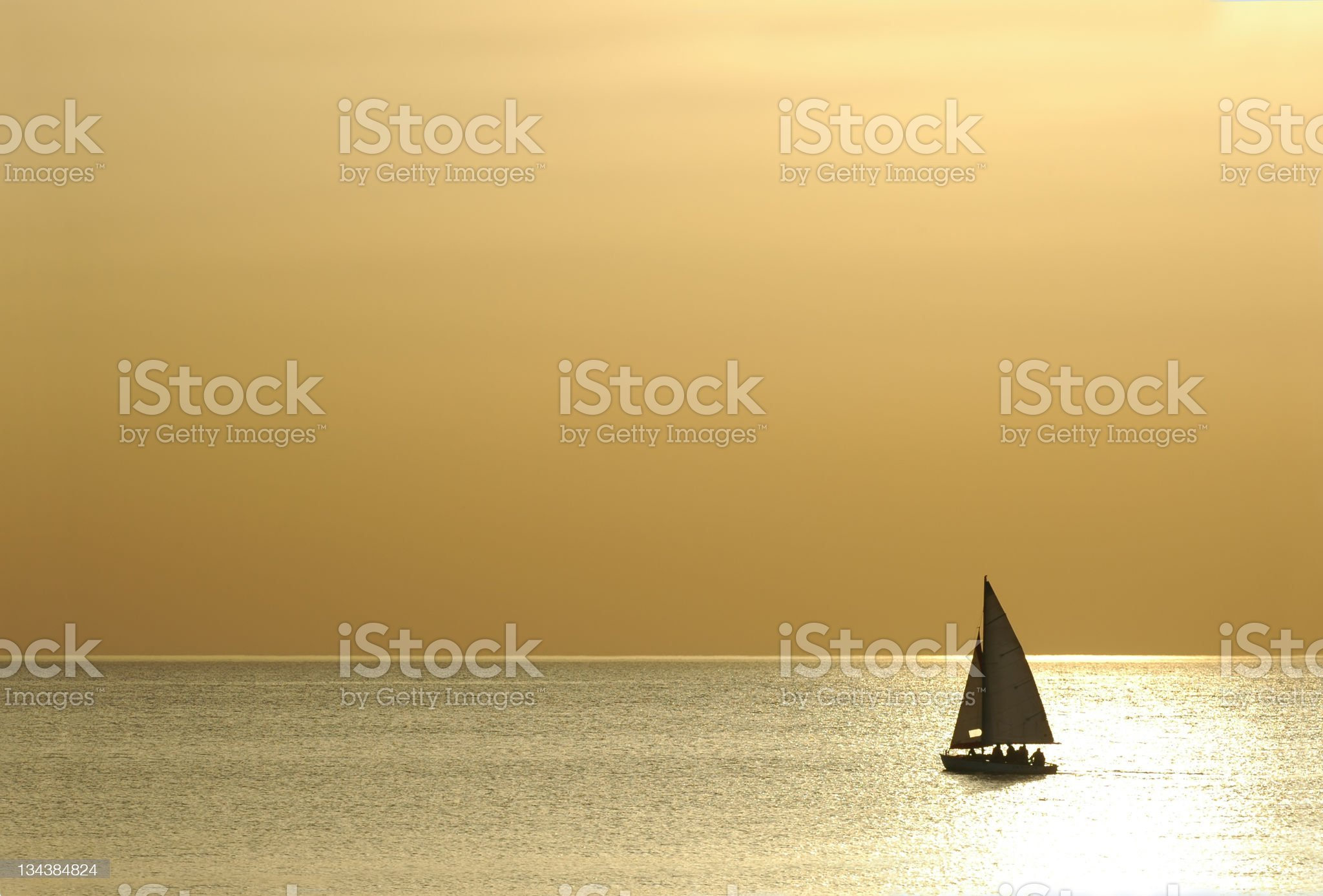 Lone sailboat on calm waters in beige coloring royalty-free stock photo