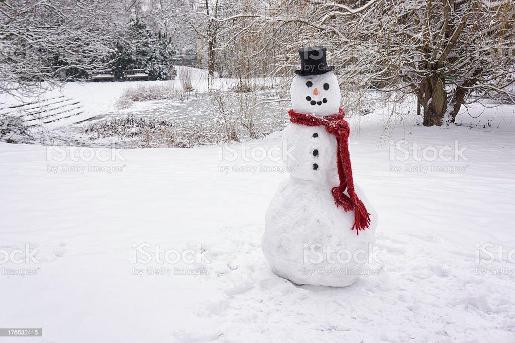 Lone snowman near frozen lake landscape stock photo
