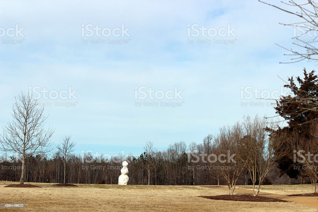 Lone Snowman Stands in Park stock photo