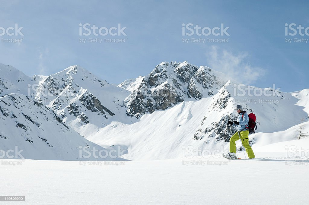 Lone snowshoer trekking through high snowy mountain stock photo