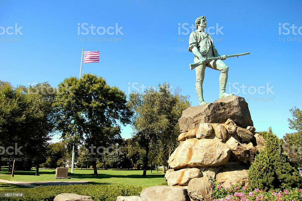 Lone statue on top of rock with American flag flying behind stock photo