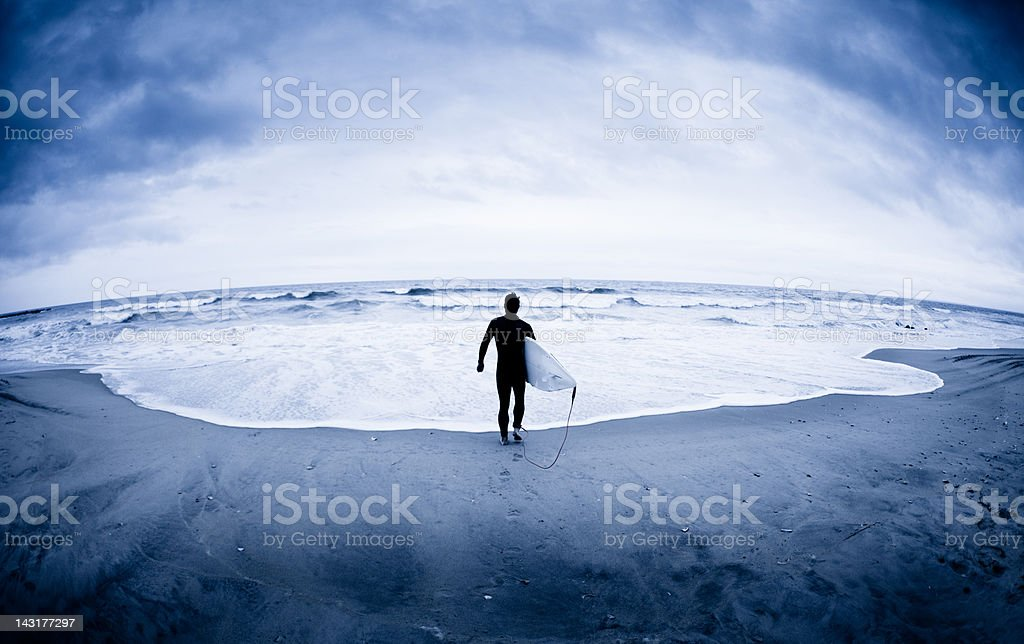 Lone surfer at edge of Atlantic Ocean in winter stock photo