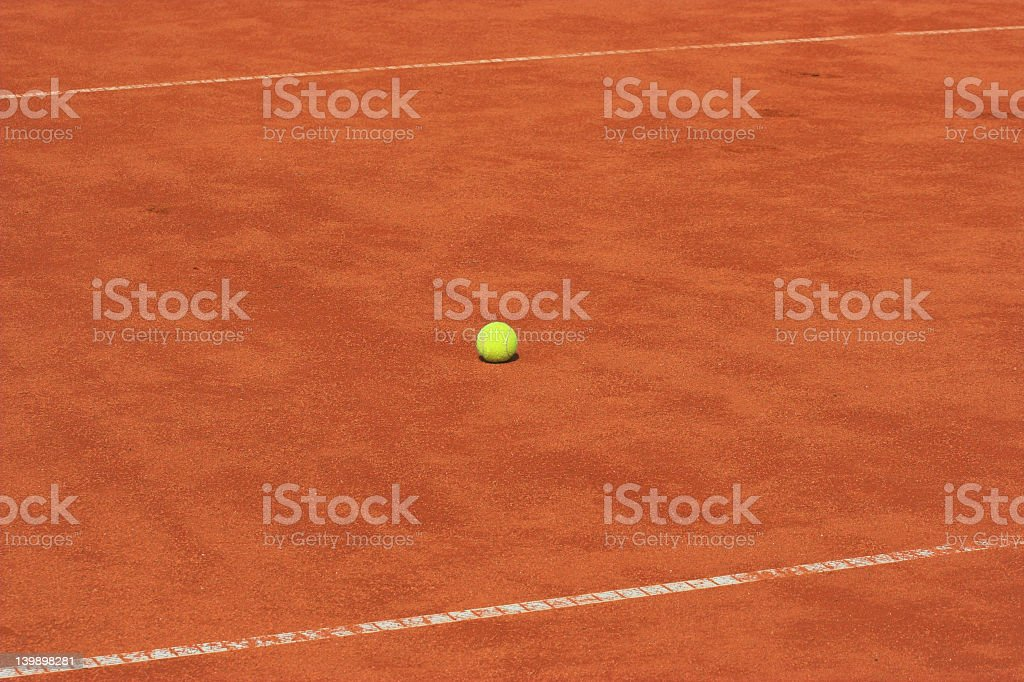 Lone tennis ball on an empty clay tennis court stock photo